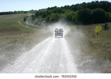 Off road vehicle moving in cloud of dust from previous car.