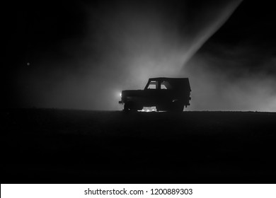 Off roader jeep silhouette on dark toned foggy sky background. Car with light at night. Selective focus