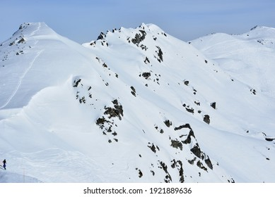 Off trail skiing in the high mountains with tracks in the fresh snow