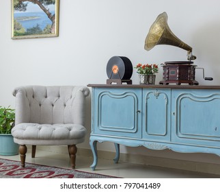 Off white armchair, vintage wooden light blue sideboard, old phonograph (gramophone), vinyl records on beige wall