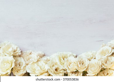 Off white creamy spray roses framing a blurred wooden background with free space