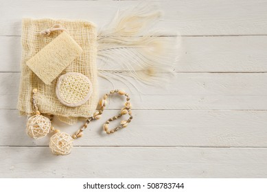 Off white spa or body cleansing products with a seashell necklace and white peacock feathers on a white wood background with copy space.