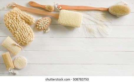 Off white spa or body cleansing products with loofah mitt, massagers, brushes and scrubbers and white peacock feathers with copy space.