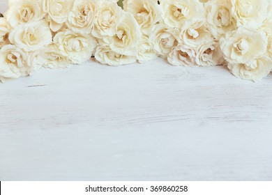 Off white spray roses framing white wooden rustic background with free space