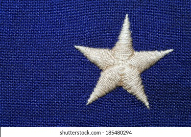 An off white star embroidered on a course weave blue background. This is a detail shot of a USA flag.