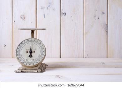 An off white vintage kitchen scale on a white contertop.