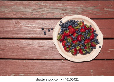 An off-center ceramic platter of bright red strawberries with blueberries spilling over the edge on a rustic rust-red stained chipping wood table