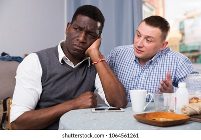 Offended African American man sitting at table at home while his friend talking to him
