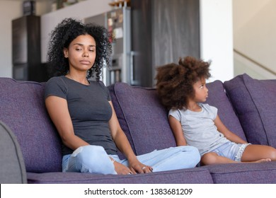Offended African American young mom and small daughter sit aside on couch avoid talking after fight, stubborn mad black mother and little kid ignore each other after quarrel. Family problem concept