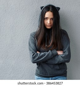 offended  black-haired girl in hoodie looking at camera. Wall background.