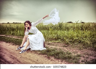 The offended bride with an old suitcase throwing out a wedding veil on the rural road