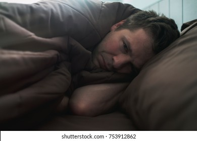 offended caucasian man lie on bed and cover himself with blanket. He is about to cry. Negative human emotion.