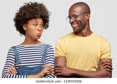 Offended dark skinned female purses lips, keeps arms folded, dressed in striped shirt, has Afro hairstyle, looks with displeased expression at husband who has cheerful expression, doesn`t feel guilty