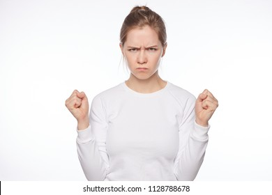 Offended European lady looking cute when angry. Portrait of outraged tender feminine woman, raising clenched fists and frowning, being insulted or mad, sulking from unhappiness over white background.