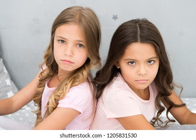 Offended feelings. Children offended keep silence. Relations sisters or best friends. Overcome relations issues. Childhood friendship. Friends sit back to back. Offended kids look seriously and sadly.