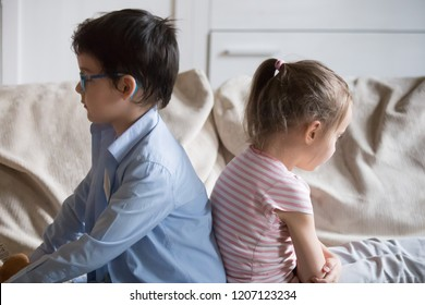 Offended little preschool siblings after quarrel, punishment sitting together on sofa in living room at home dont look at each other. Sulky sister and brother have conflict feeling frustrated unhappy