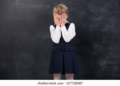 Offended little schoolgirl standing at the blackboard and crying