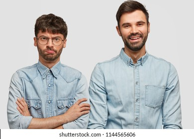 Offended man feels angry with his brother after family quarrel, looks with displeased facial expression, cheerful bearded male near. Two friends express different emotions and feelings, pose indoor