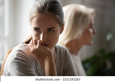 Offended millennial adult daughter and senior mother sit aside back to back avoid talking after fight, hurt stubborn two generations of women ignore each other after conflict, misunderstanding concept