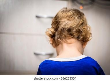 offended punished little boy sitting back, photo indoor children's bedrooms. blonde, short curls.