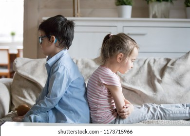 Offended small siblings sit on couch back to back upset after fight, brother and sister not talking to each other after quarrel, little boy and girl ignore each other not compromising. Rivalry concept