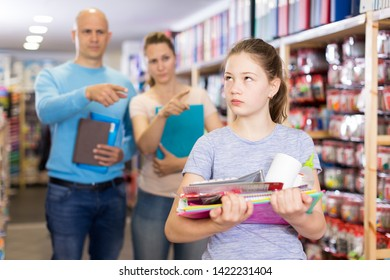Offended tween girl standing with school accessories in store while parents berating her