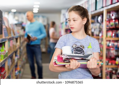Offended  unhappy tween girl standing with school accessories during shopping with parents in stationery shop