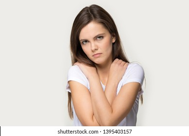 Offended vulnerable sad millennial girl looks at camera pose over grey studio background self hug closed pose folded crossed arms on chest, woman feels lonely cheated suffering from bullying or abuse