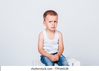 Offended white-haired boy sits on a box isolated on a gray background