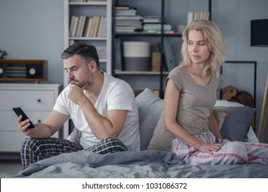 Offended wife looking at her cheating husband with a phone. Crisis in a marriage concept
