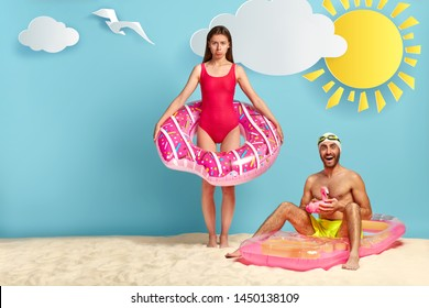 Offended woman in red swimsuit, stands with inflated ring, sad husband doesnt pay attention to her, cheerful guy with naked torso sits on mattress. Family couple rest on coastline during summer