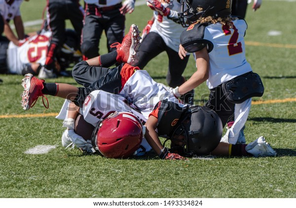 Offensive youth football player is tackled and at bottom of pile during game at stadium.