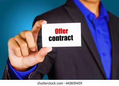 """Offer contract"" black and red text on white card hold by young business man wearing a business jacket - economic, finance and crisis concept"
