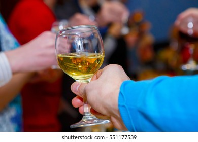 Offer to drink alcohol. The man holds out a glass at the festival. Alcoholic feast at the Banquet. Celebration with alcohol. Joint booze at the party.