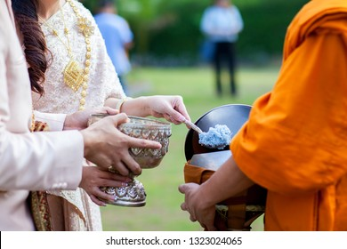 Offer food to monk. Groom give alms food to a Buddhist monk in traditional thai wedding ceremony. Hand while put food offerings in a Buddhist monk's alms bowl.Buddhists offer food in bowls.