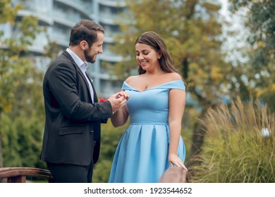 Offer of marriage. Attractive young bearded man giving ring proposing to cute pretty smiling woman outdoors.