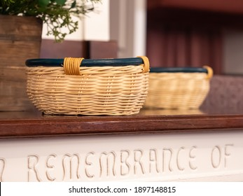 Offering baskets resting on a wooden table in front of the church pulpit