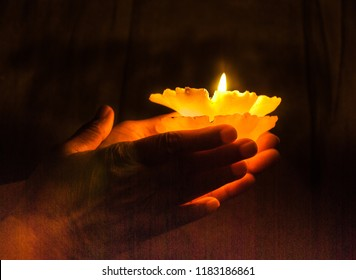 Offering a brightly lit candle .Glowing hands holding a brightly lit candle against a dark background. Lighting candles on Diwali.