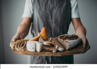 Offering cheese and bread served on a wooden board. Wine dinner or aperitivo party concept.