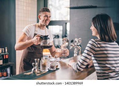 Offering coffee. Enthusiastic young barista standing at the bar counter with a glass coffee jug in his hand and smiling to a visitor while offering her some coffee