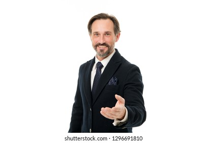 Offering his hand. Bearded mature man in business style. Mature businessman in formal wear. Senior man with grey beard hair. Fashionable aged business person. Back to work in a suit and tie.