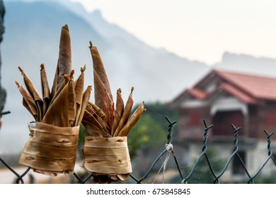 Offering made with banana leaf hanging on fence.House Mountain as Background.Laos.