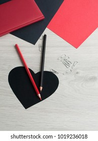 Office accessories: black pencil, red pencil, staples, notepad, red and black paper, black heart on a gray wooden table. Valentine's Day. Top view. Copy space.