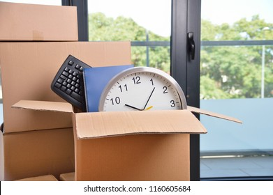 Office accessories in a cardboard box at office.
