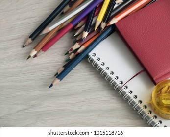 Office accessories: Colored pencils, sharpener, red notepad and a white notebook on wooden gray table. Back to school. Top view. Copy space.