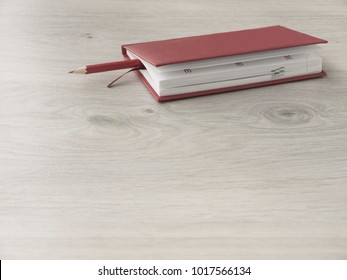 Office accessories: a red notepad and red pencil on a wooden gray desk. Top view, Copy space.