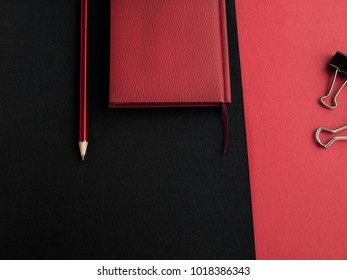 Office accessories: Red notepad, pencil and binders on a red-black background. Top view. Copy space.