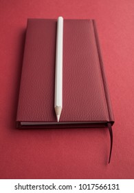 Office accessories: Red notepad, white pencil on a red background. Education. Business. The concept. Top view. Copy space.