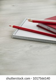 Office accessories: a red notepad, a white notepad and pencils on a wooden gray desk. Back to school. Top view. Copy space.