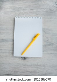 Office accessories: yellow pen, blank notepad on a wooden gray desk. Top view. Copy space.